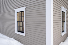 Two Horizontal Opening Vintage Windows In A Tan Colored Wooden Building. The Windows Have White Trim Around Them. The Exterior Wall Of The Building Is A Beige Clapboard. A Snow Drift Is On The Ground.