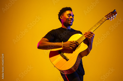 Fotografiet Young and joyful african-american musician playing guitar and singing on gradient orange-yellow studio background in neon light