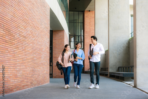 Obraz na płótnie Asian three students are walking and talking together in university hall during break in University
