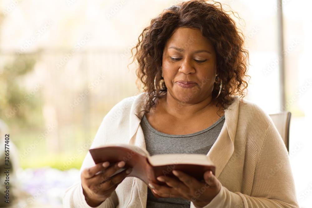 Fototapeta Mature African American woman sitting outside reading.