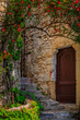 canvas print picture - Old wooden door of a stone house covered with flowers in South of France Eze Village, medieval city by Mediterranean Sea