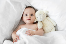 Baby Lying On White Bed With Stuffed Animal