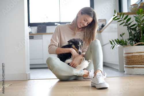 Fotografía Woman at home sittign on floor with puppy dog