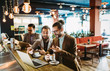 canvas print picture - Group of attractive young business men colleagues working together in cafe
