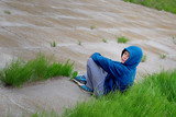teenager sits on a concrete slab mound
