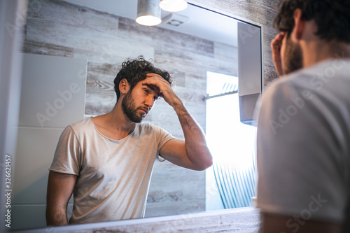 Fényképezés Handsome young man touching his hair with hand and grooming in bathroom at home