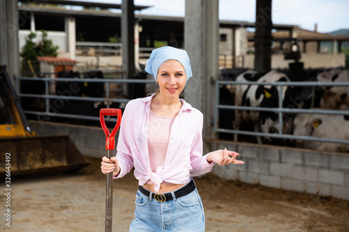 Photo Young woman farmer with shovel standing near agrimotor at farm