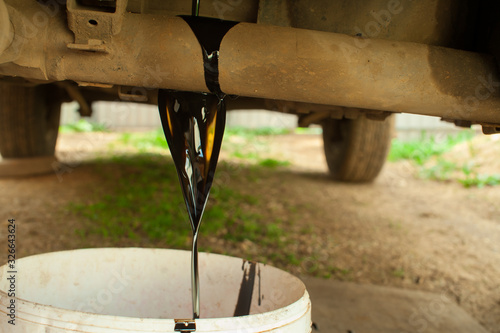 Cuadros en Lienzo Old car oil is poured into a bucket. Changing the oil in the car.