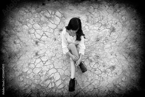 Photo Black and white photo of sadness teenager sitting on the cracked ground