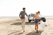 Attractive Young Couple Playing With Their Dog