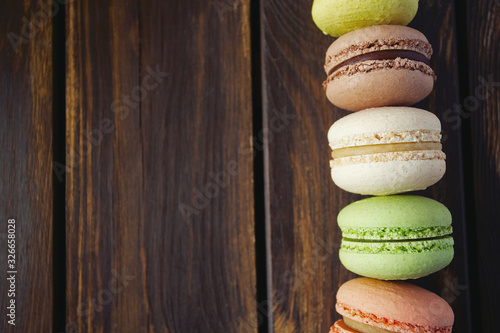 Photo assortment of macaroon cookies on wooden surface