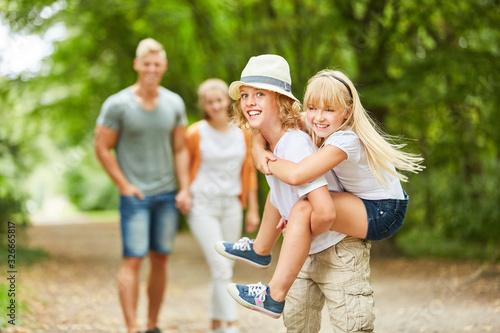 Obraz Fröhlicher Junge mit Mädchen auf dem Rücken - fototapety do salonu