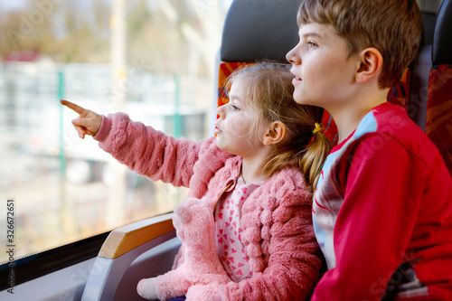 Fototapeta Cute little toddler girl and brother kid boy sitting in train and looking out of window. Two adorable happy healthy children having fun together. Smiling siblings going on family vacations by railroad obraz