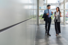 Business People Walking In Hallway With Big Windows Stock Photo