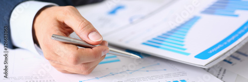 Foto Male hands hold documents with financial statistics at office workspace closeup