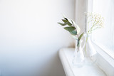 Two vases with dry branches on white windowsill in daylight home interior