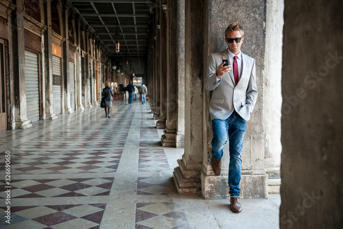 Well dressed man using his mobile phone leaning against a column of the classic Canvas-taulu