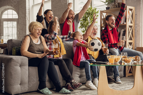 obraz PCV Excited, happy big family watching football, soccer match on the couch at home. Fans emotional cheering for favourite national team. Having fun from grandparent to children. Sport, TV, championship.