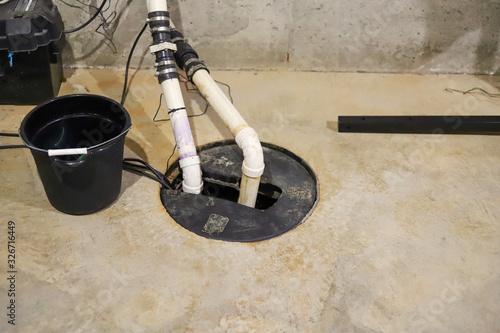 A sump pump in a  home basement-plumbing repair Wallpaper Mural