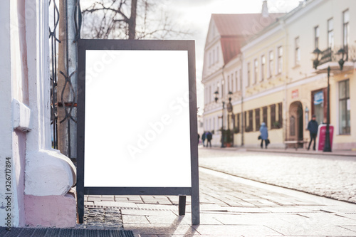 Fototapeta blank poster stands with space for design on street pavement at building on sunny day obraz