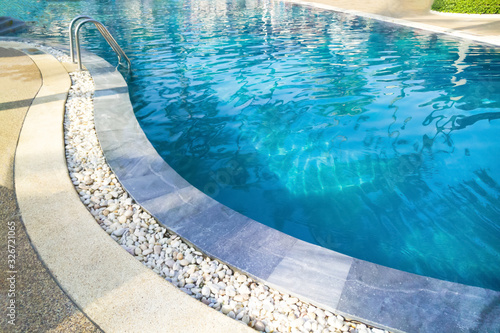 Obraz Swimming pool with metal ladder..Fragment of kidney-shaped swimming pool with stair. Cleaning blue color water. Сlose up in blur. - fototapety do salonu