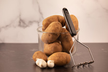 Raw Russet Potatoes In Glass Bowl With Old Kitchen Hand Potato Masher