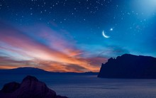 Ramadan Background With Crescent, Stars And Glowing Clouds With Ray From Skies Above Mountains And Sea. Month Of Ramadan Is That In Which Was Revealed Quran.