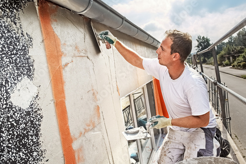 A craftsman is plastering thermal insulation Polystyrene panels of an old building
