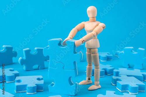 Wooden man assembling jigsaw puzzle Canvas Print