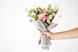 Female hand holding beautiful flower bouquet on white background