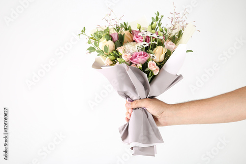 Female hand holding beautiful flower bouquet on white background Canvas Print