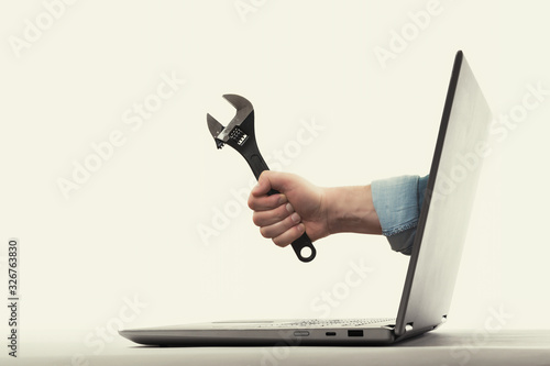 Fototapeta The human hand with  black wrench stick out of a laptop screen. Concept of technical support. obraz