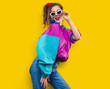 Cool teenager. Fashionable DJ girl in colorful trendy jacket and vintage retro sunglasses enjoys style of 80s � 90s vibes. Teenager Girl at disco party. Young fashion model on yellow color background.