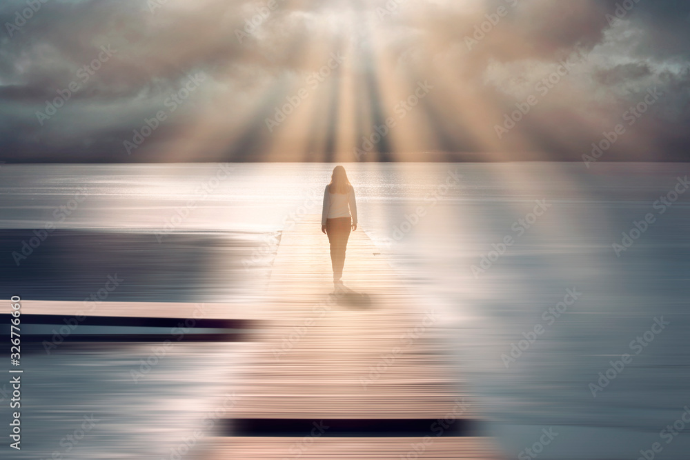 Fototapeta Spiritual sunny light with beams and back view of a walking woman.