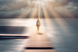Fototapeta Las - Spiritual sunny light with beams and back view of a walking woman.