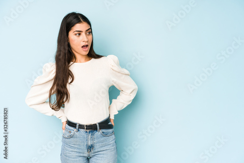 Young indian woman isolated on blue background being shocked because of something she has seen Canvas Print