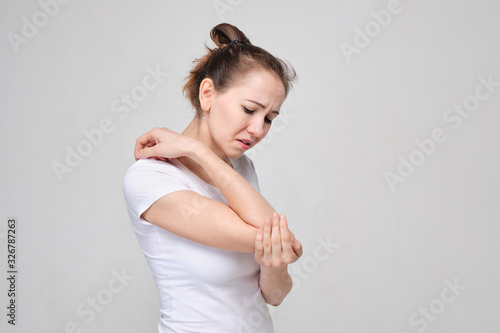 Photo A girl in a white T-shirt massages her elbow from acute pain in the joint