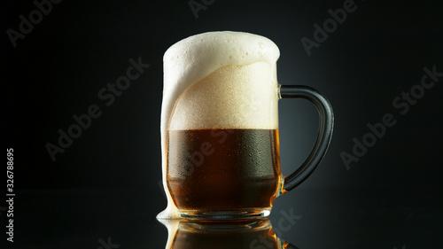Fototapeta Beer foam overflowing from glass pint obraz