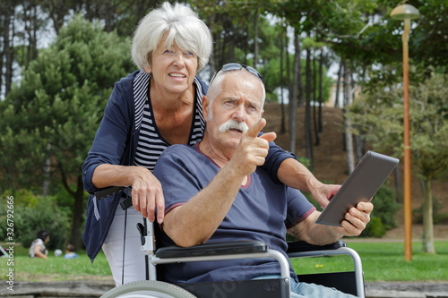 elderly couple outdoors with tablet pc man in wheelchair Canvas Print