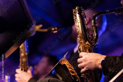 Photo A baritone saxophone player playing their horn during a jazz concert in a venue