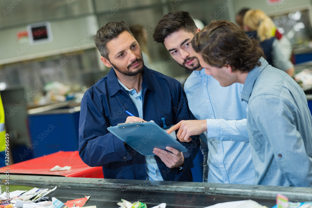 Fototapeta three male workers in discussion while looking at clipboard