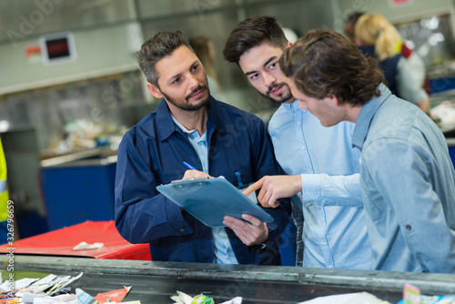 Photo three male workers in discussion while looking at clipboard