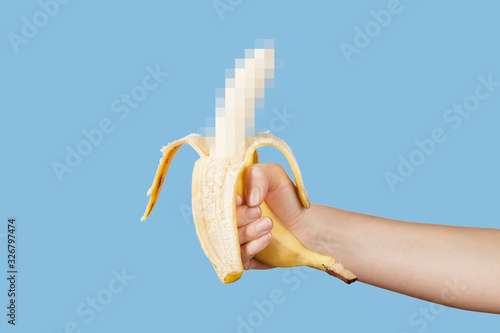 Photo Hidden censored banana in hand on a blue background