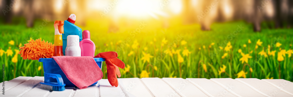 Fototapeta Cleaning supplies and chemicals on nature background web banner: spring cleaning concept