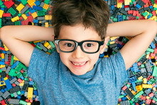 Smart Little Boy With Eyeglasses Resting Between With Hands Under The Head On Colored Plastic Building Blocks
