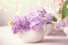 Room Interior With Purple Lilacs Flower Blossom In Kettle On Table And Yellow Butterfly, Tender Romantic Spring Home Decor In Soft Morning Light, Shiny Glowing Bokeh, Decorating House With Syringa