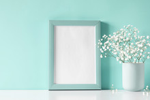 Photo Frame And Small White Flowers In Vase On Pastel Blue Background. White Gypsophila Flowers On Shelf Or Desk. Mock Up With Decor Elements.