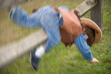Toddler Boy Dressed Up As A Cowboy Falling Over A Post In A Field In New Jersey.