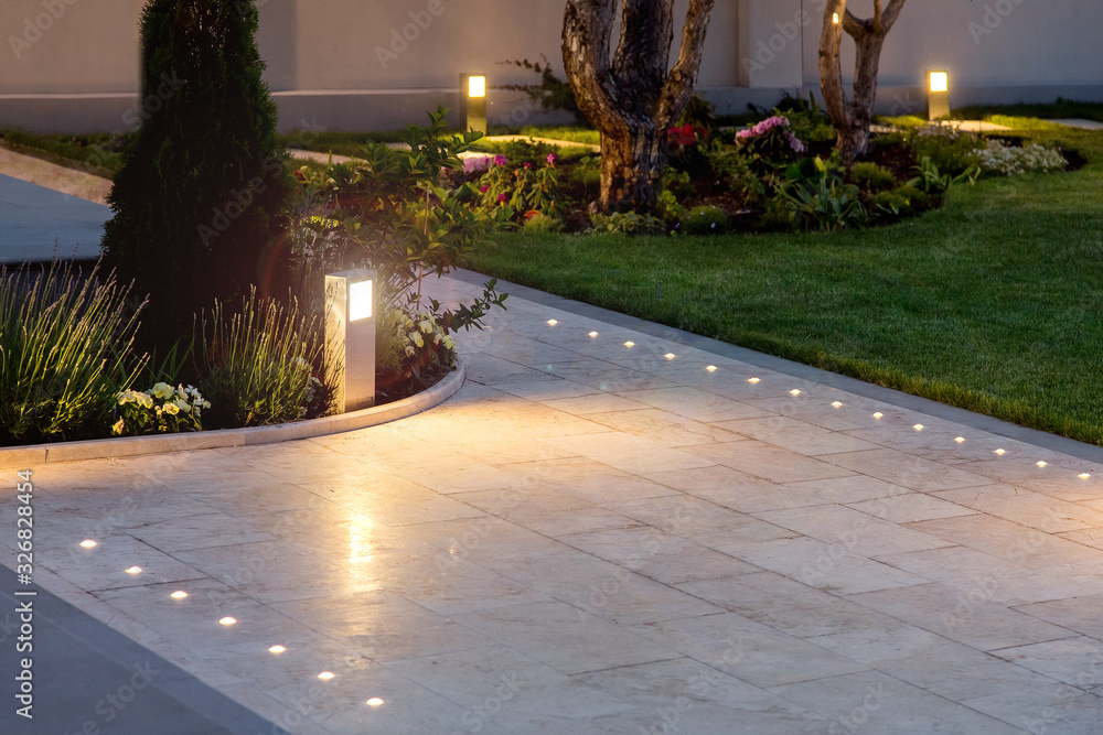 Fototapeta marble tile playground in the night backyard of mansion with flowerbeds and lawn with ground lamp and lighting in the warm light at dusk in the evening.