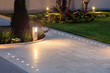 canvas print picture - marble tile playground in the night backyard of mansion with flowerbeds and lawn with ground lamp and lighting in the warm light at dusk in the evening.